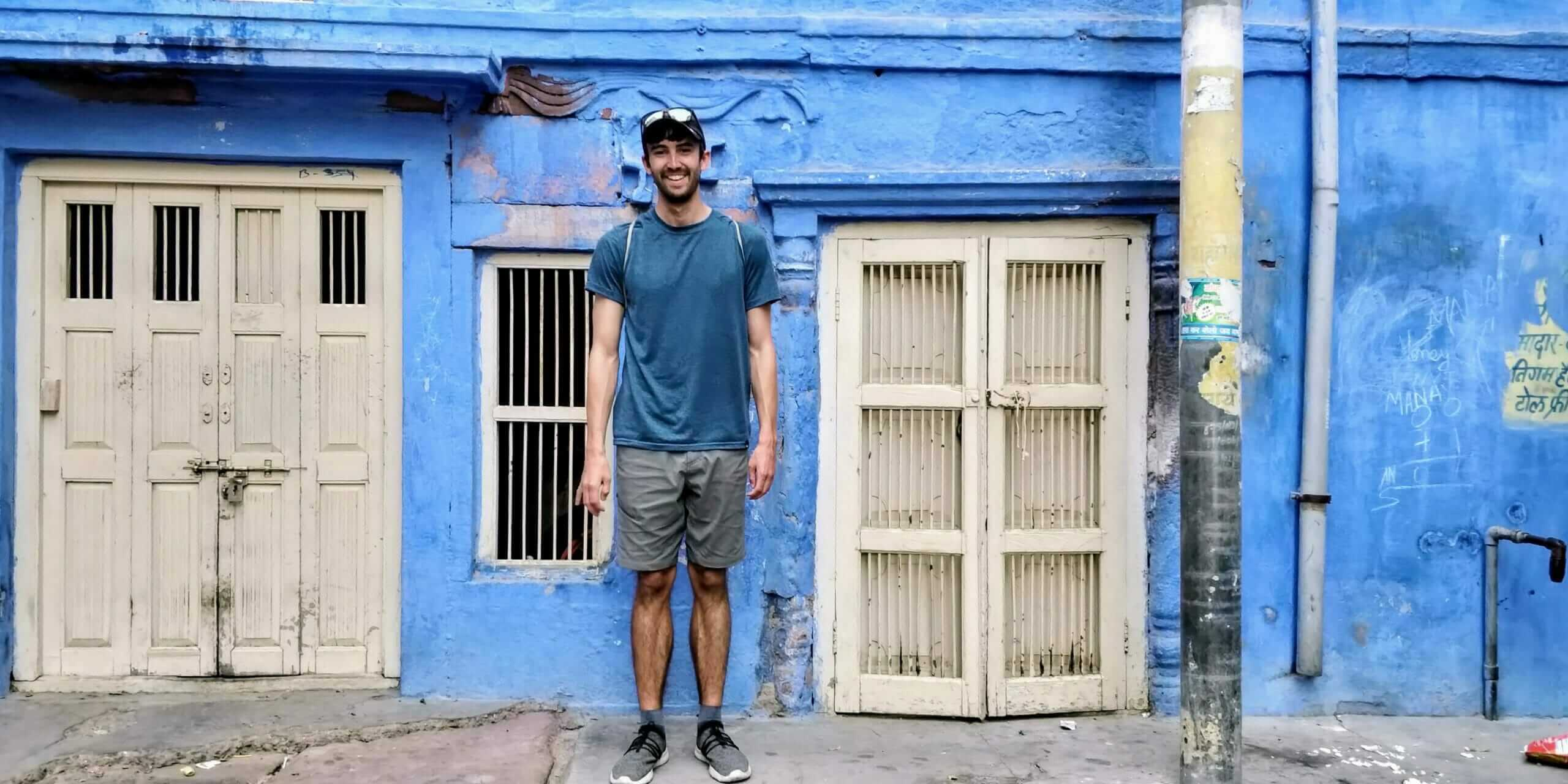 Blue building in Jodhpur with Tony wearing a blue shirt