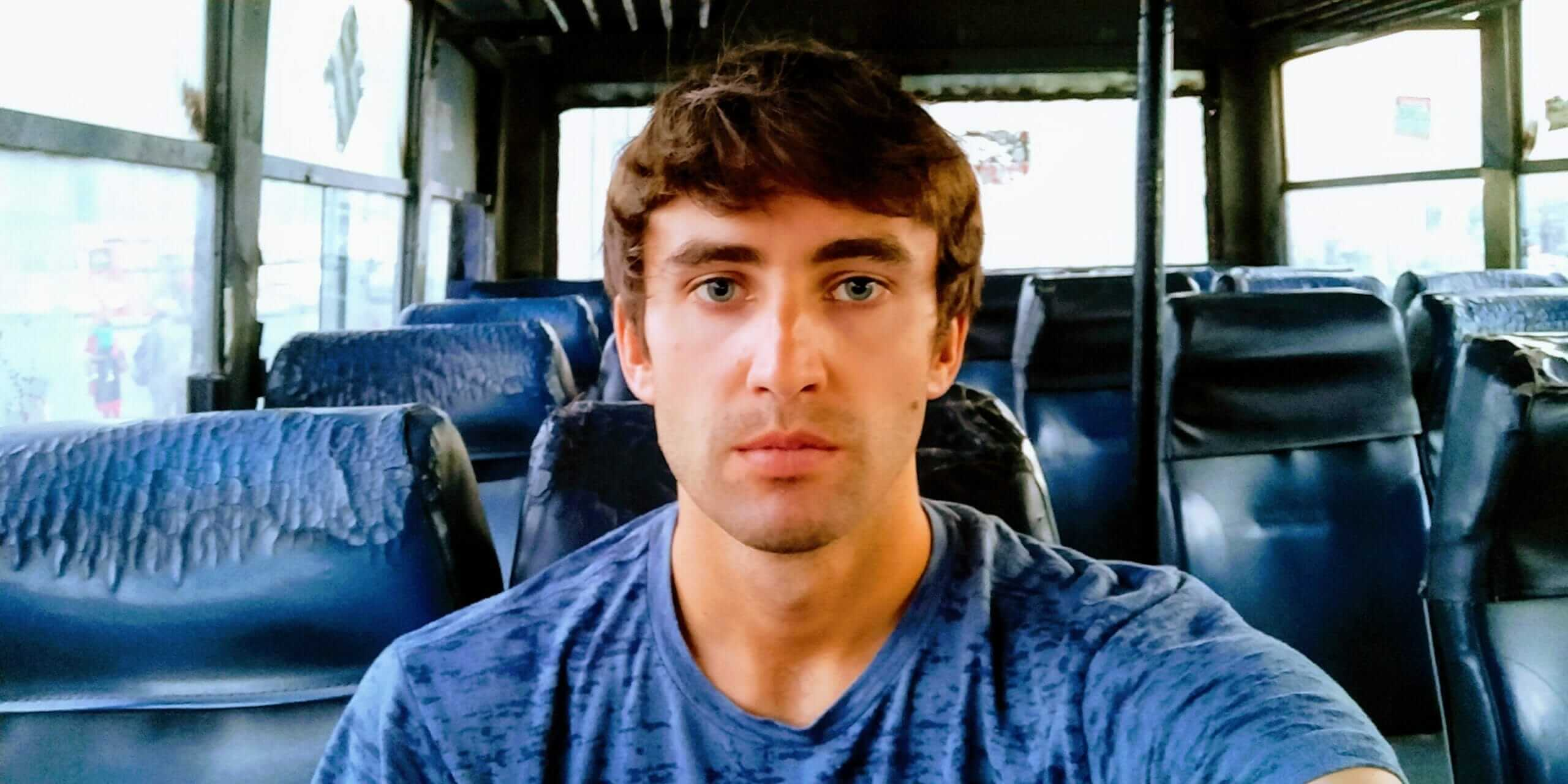 Selfie in a beat-up empty Indian bus while backpacking India