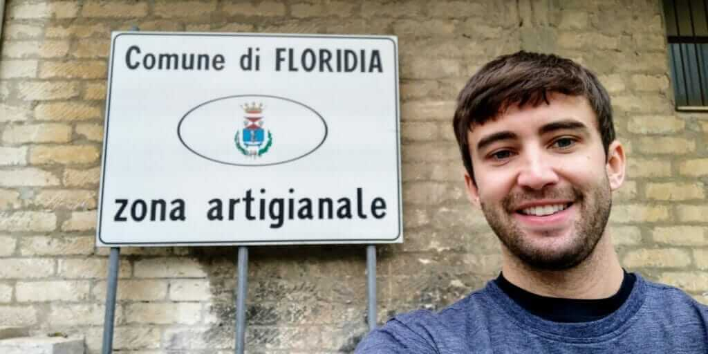 Tony Florida taking a selfie in front of a Comune di Floridia sign in Sicily, Italy