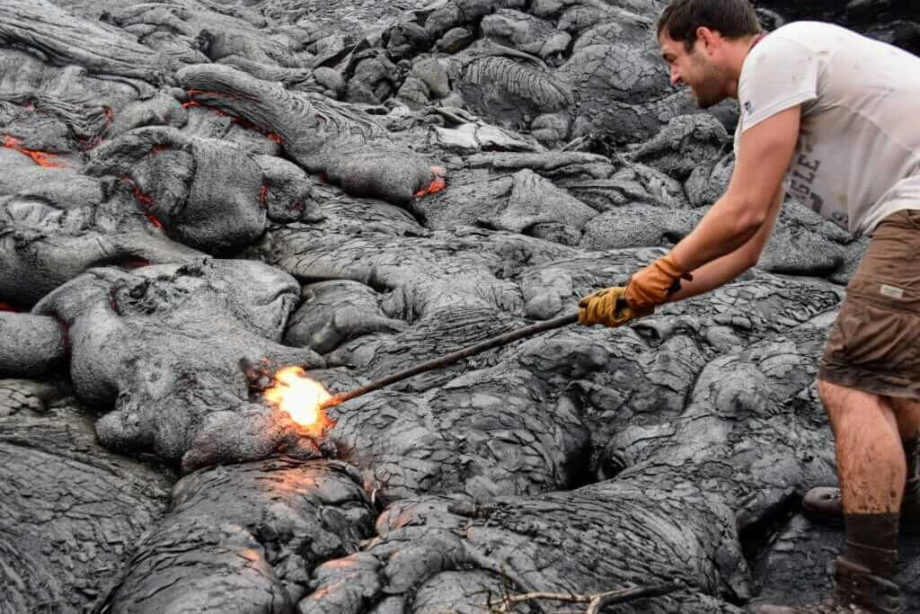 Poking a stick into molten lava during Hawaii lava tour