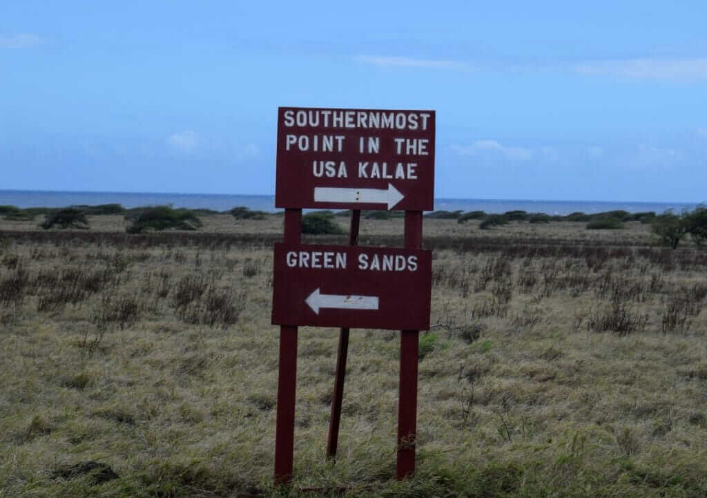 Wooden sign with southernmost point in the USA Ka Lae and green sand beach