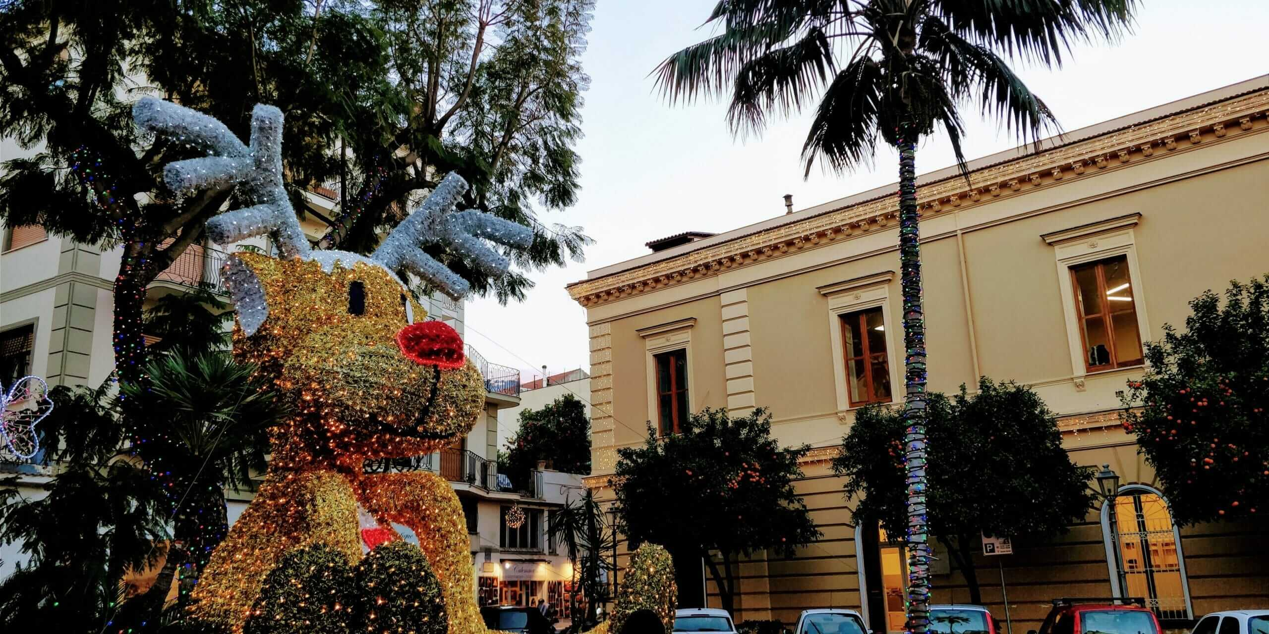 Orange and palm trees decorated with Christmas lights at the end of January in Sorrento