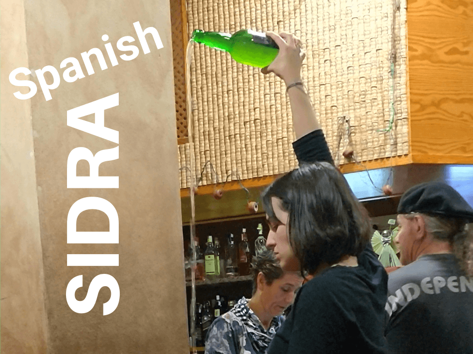 Woman pouring sidra from above her head in Spain