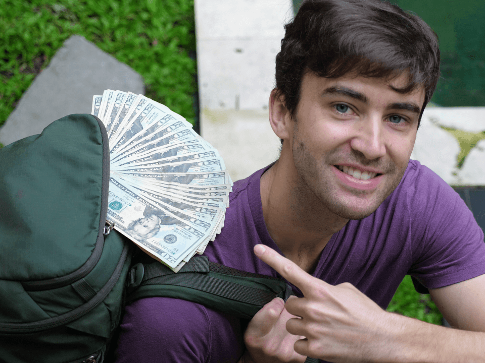 Traveler with money hanging out of his backpack
